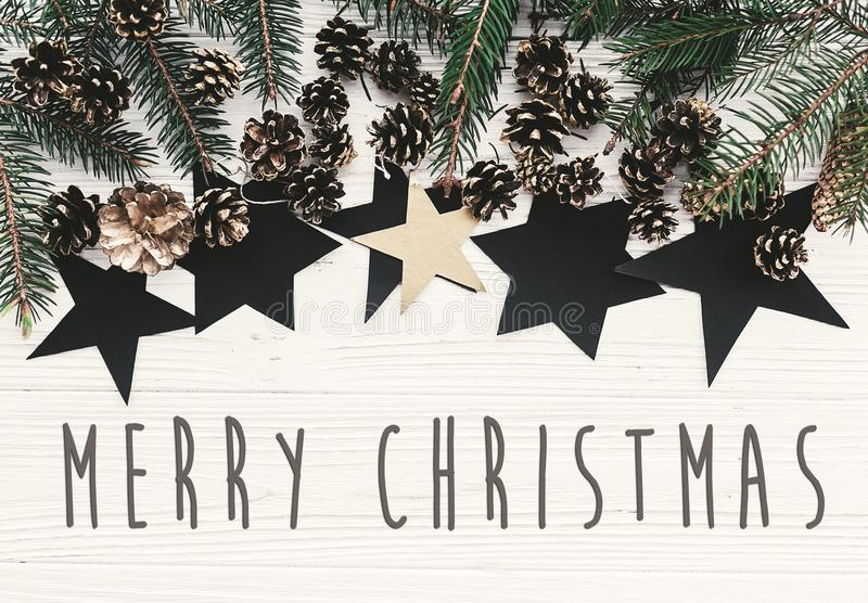 Merry Christmas text on modern christmas flat lay with green fir. Branches, golden pine cones and stars. Season`s greetings card. Happy Holidays and Happy new stock photo