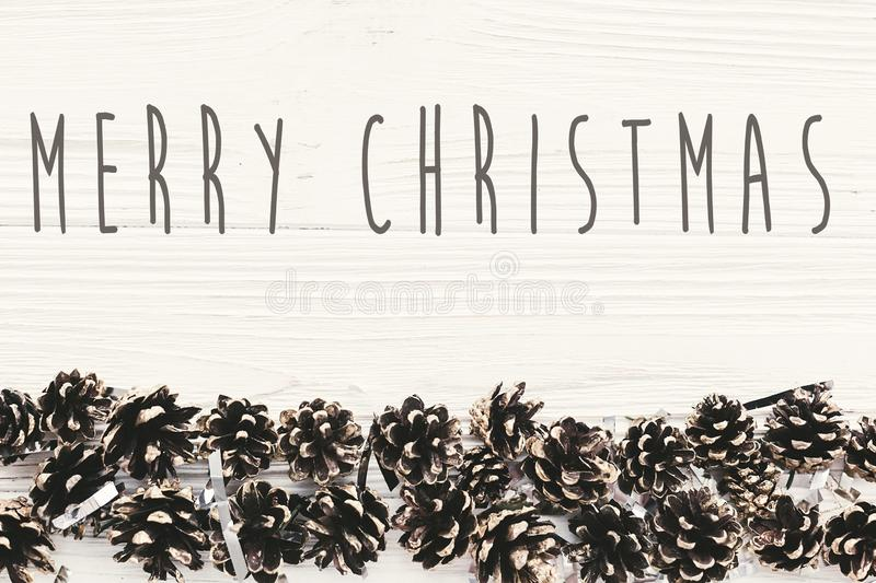 Merry Christmas text on modern christmas flat lay with green fir. Branches, golden pine cones . Season`s greetings card. Happy Holidays and Happy new year royalty free stock image