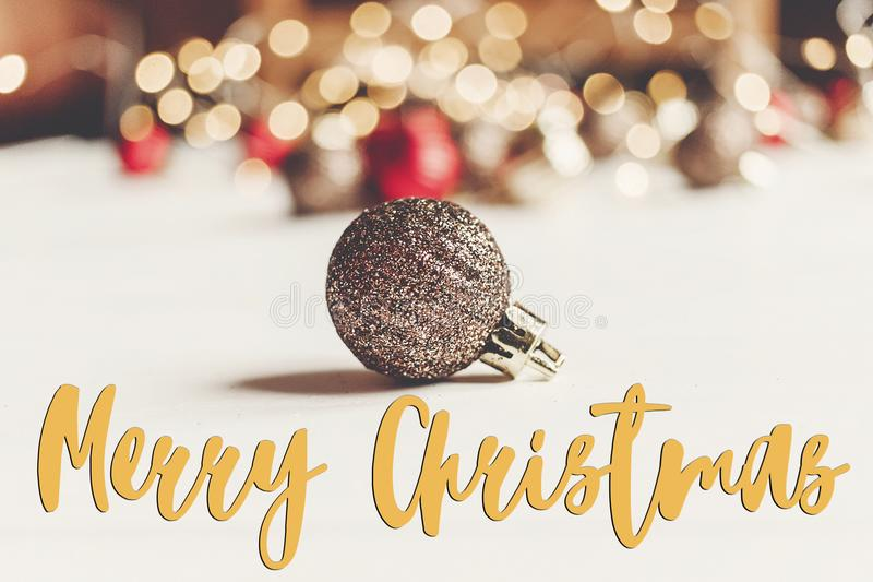 Merry christmas text, seasonal greetings card sign. glitter christmas ornament with illumination lights on white wooden. Background. merry xmas stock photos