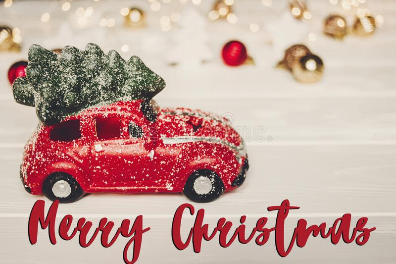Merry christmas text, seasonal greetings card sign. christmas pr. Esent. red car toy with christmas tree on top on white wood with lights in background, xmas vector illustration