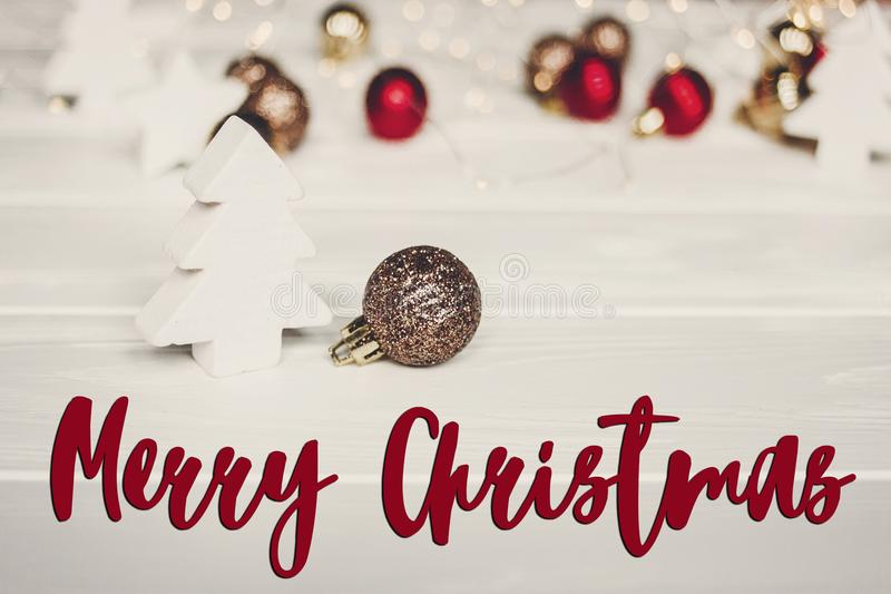 Merry christmas text, seasonal greetings card sign. simple ornaments and christmas trees on white wood with lights in background. Xmas gift. holiday royalty free stock image