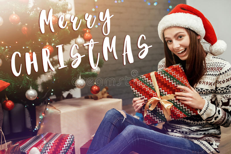 Merry christmas text sign greeting with Beautiful happy emotional woman in red santa hat and reindeer sweater smiling after. Receiving christmas presents stock images
