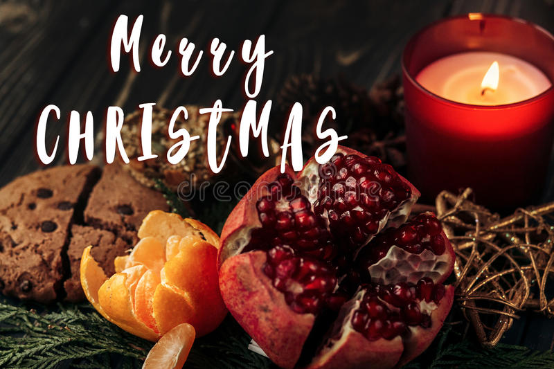 Merry christmas text sign on stylish rustic wallpaper candle g. Arnet cookies fruits on wooden background with green branches. seasonal greetings for winter royalty free stock images