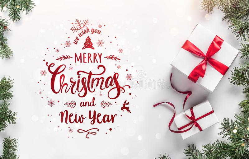 Merry Christmas text on white background with gift boxes, fir branches, red decoration. Xmas and New Year greeting card, bokeh, royalty free stock photo