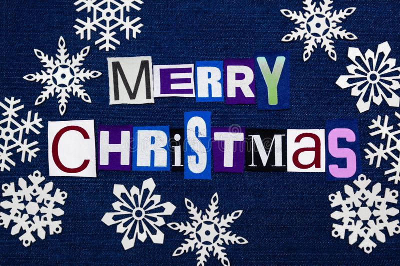 Merry Christmas text word collage surrounded by white paper snowflakes, multi colored fabric on blue denim, winter holiday royalty free stock photography