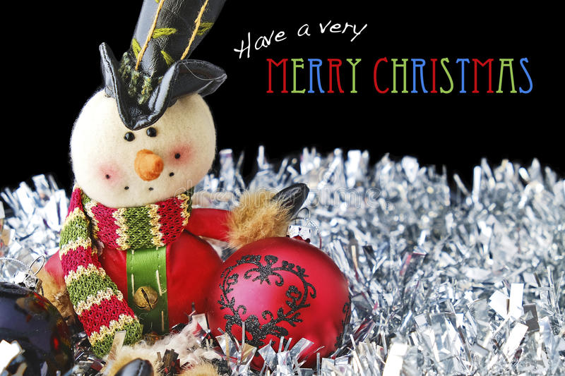 Merry Christmas with Toy Snowman and Baubles on Tinsel. Merry Christmas message with toy snowman and red and black baubles on silver tinsel with a black royalty free stock photography
