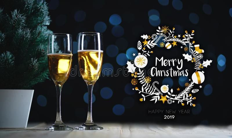 Merry Christmas Typography Art. Two Glasses of Champagne and Small Christmas Tree Dark Glow Lights Background. royalty free stock image