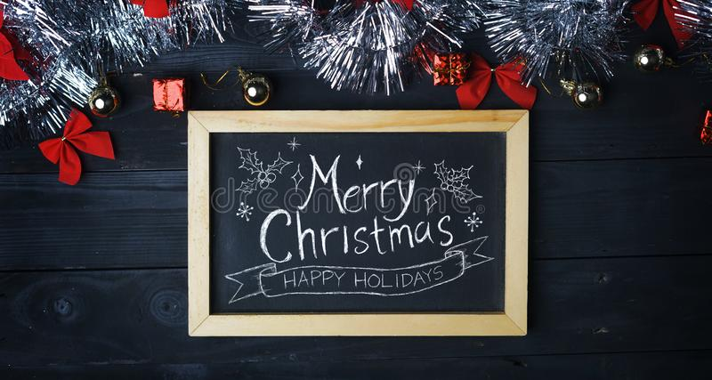 Merry Christmas Typography on Blackboard. Silver Christmas Ornament on Black Wood Plank.  royalty free stock photos