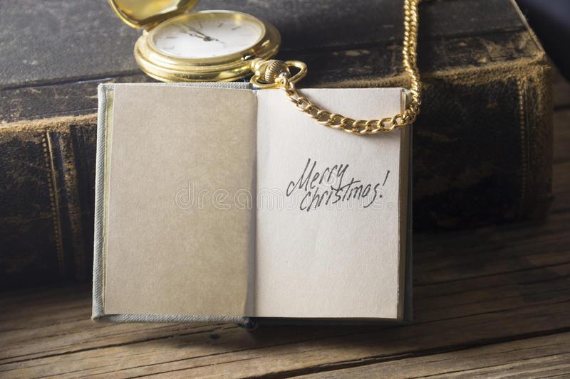 Merry Christmas vintage Card. Merry Christmas - inscription, gold pocket watch and old vintage book stock photo