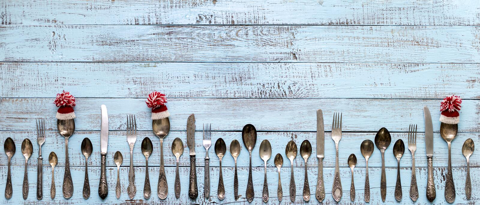 Merry Christmas! Vintage cutlery in santa claus hats on old wooden background. Background with copy space royalty free stock photo