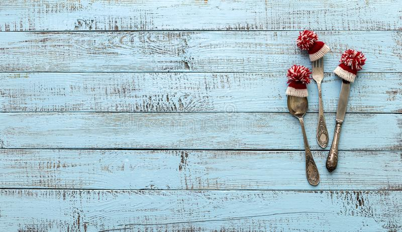 Merry Christmas! Vintage cutlery in santa claus hats on old wooden background. Background with copy space stock photography