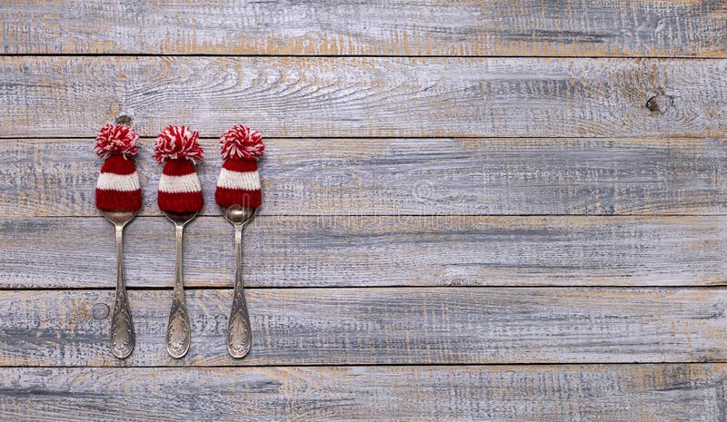 Merry Christmas! Vintage cutlery in santa claus hats on old wooden background. Background with copy space royalty free stock photos