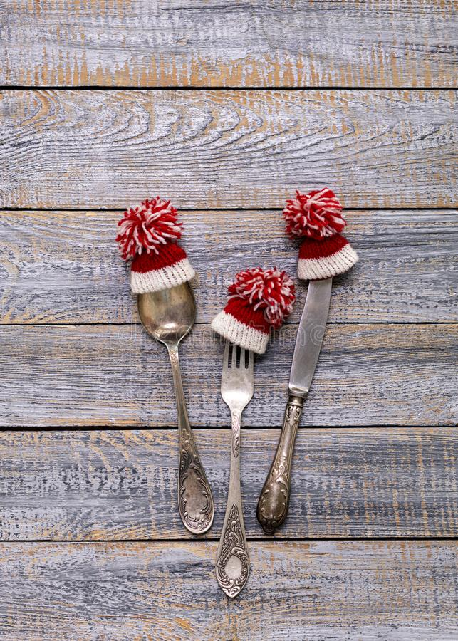 Merry Christmas! Vintage cutlery in santa claus hats on old wooden background. Background with copy space stock photo