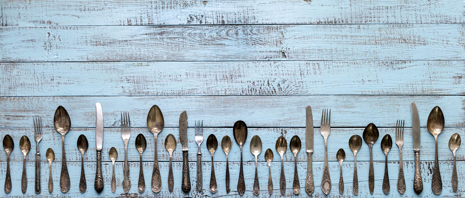 Merry Christmas! Vintage cutlery in santa claus hats on old wooden background. Background with copy space royalty free stock photography