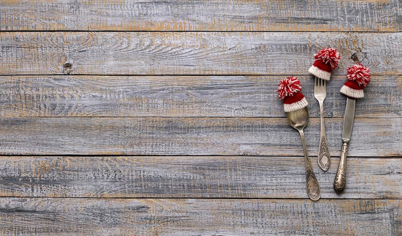 Merry Christmas! Vintage cutlery in santa claus hats on old wooden background. Background with copy space stock images