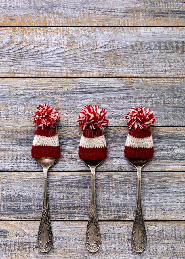 Merry Christmas! Vintage cutlery in santa claus hats on old wooden background. Background with copy space royalty free stock image