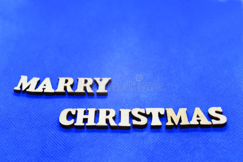 Merry Christmas white wooden letters on blue background. For printing on paper or textiles stock images