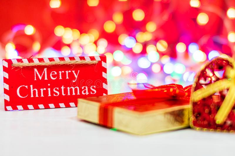 Merry Christmas wooden sign. Christmas composition on blurred lights background. Colorful Christmas balls stock photography