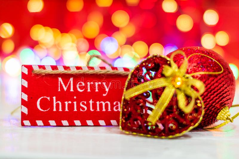 Merry Christmas wooden sign. Christmas composition on blurred lights background. Colorful Christmas balls stock images