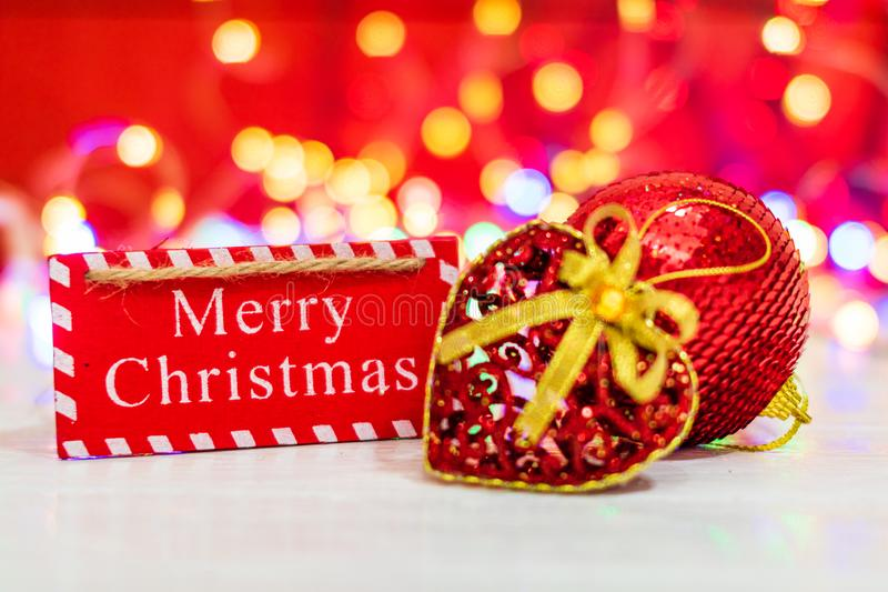 Merry Christmas wooden sign. Christmas composition on blurred lights background. Colorful Christmas balls royalty free stock images