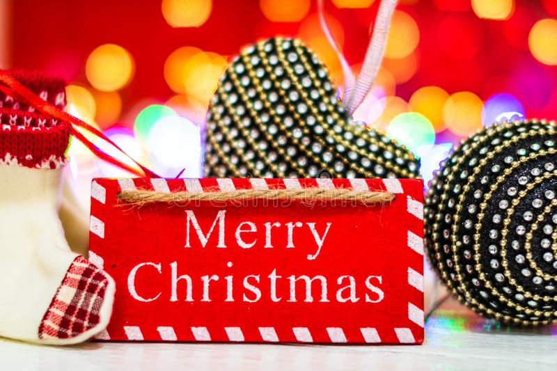 Merry Christmas wooden sign. Christmas composition on blurred lights background. Colorful Christmas balls royalty free stock image
