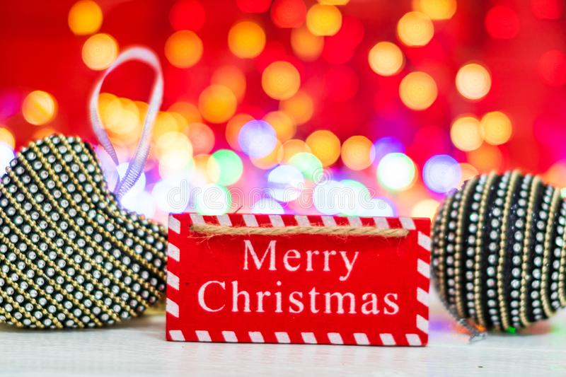 Merry Christmas wooden sign. Christmas composition on blurred lights background. Colorful Christmas balls stock image