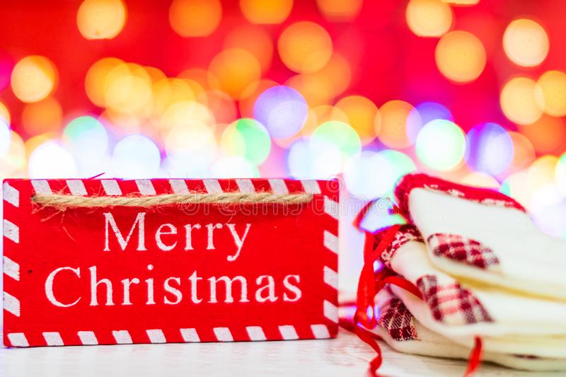 Merry Christmas wooden sign and small Christmas stockings. Christmas composition on blurred lights background stock image