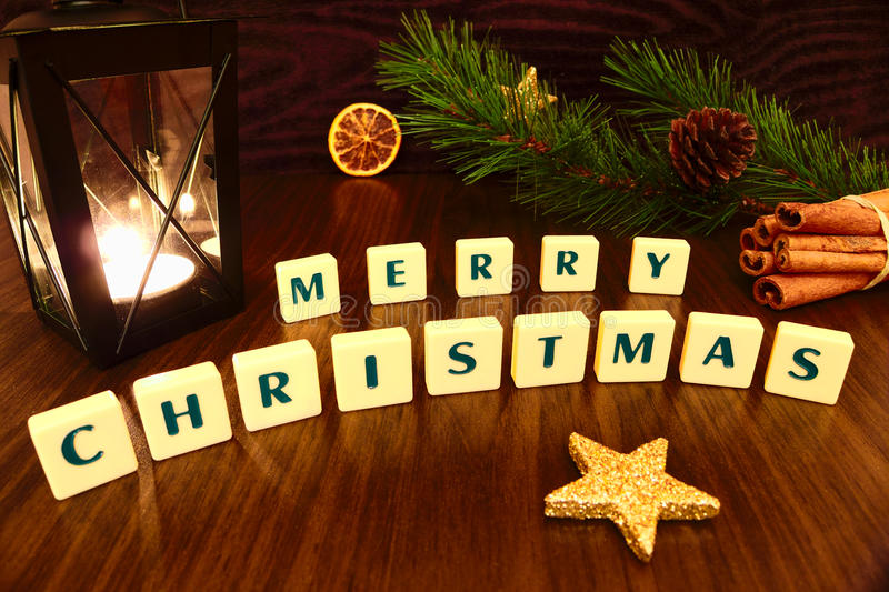 Merry Christmas words with flashlight candle, star, pine branch, cinnamon and orange. Christmas still life stock photos