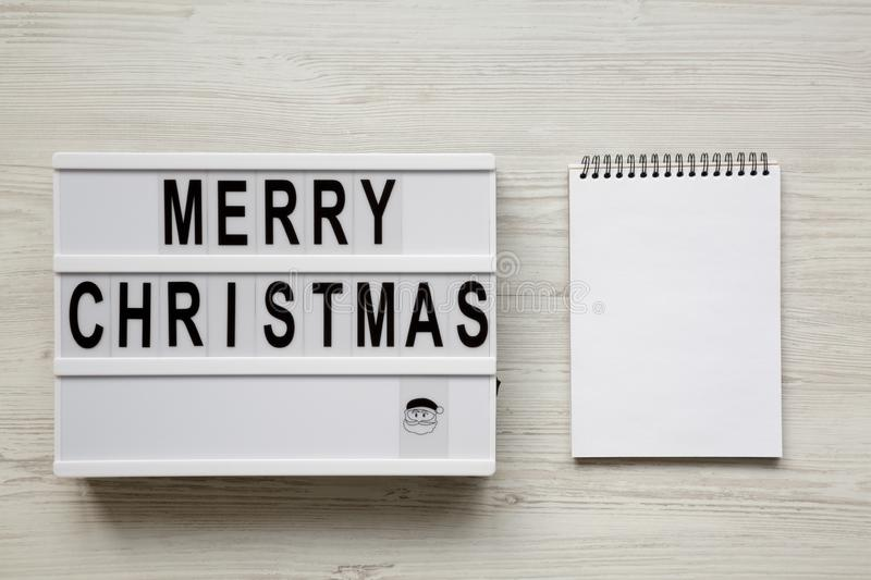 `Merry Christmas` words on lightbox, blank notepad over white wooden background, overhead view. Flat lay, from above. Top view stock photos
