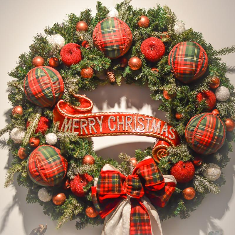 Merry Christmas Wreath With Sign. A Merry Christmas wreath with red apples, plaid, red and green ornaments and white snowball type ornaments on an evergreen royalty free stock photos