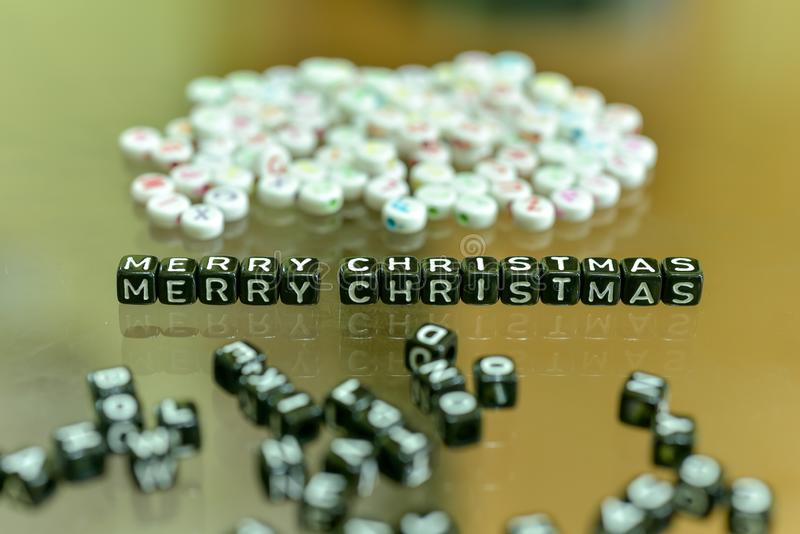 MERRY CHRISTMAS  written with Acrylic Black cube with white Alphabet Beads on the Glass Background.  stock photography