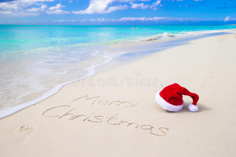 Merry Christmas written on beach white sand with. Santa Hat on white sandy beach and Merry Christmas written in the sand stock images