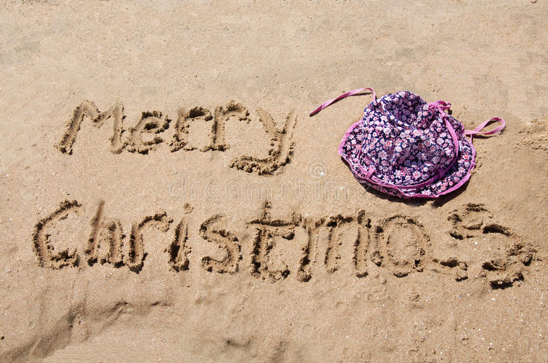 Merry Christmas written in the sand. With baby hat royalty free stock images