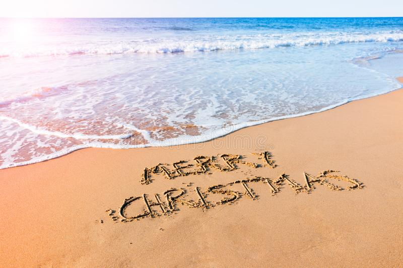 Merry Christmas on the beach. Merry Christmas written in the sand at the seashore on the beach stock photos