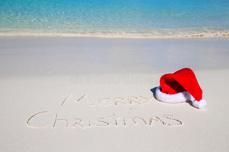 Merry Christmas written on tropical beach white. Sand with red xmas hat stock photography