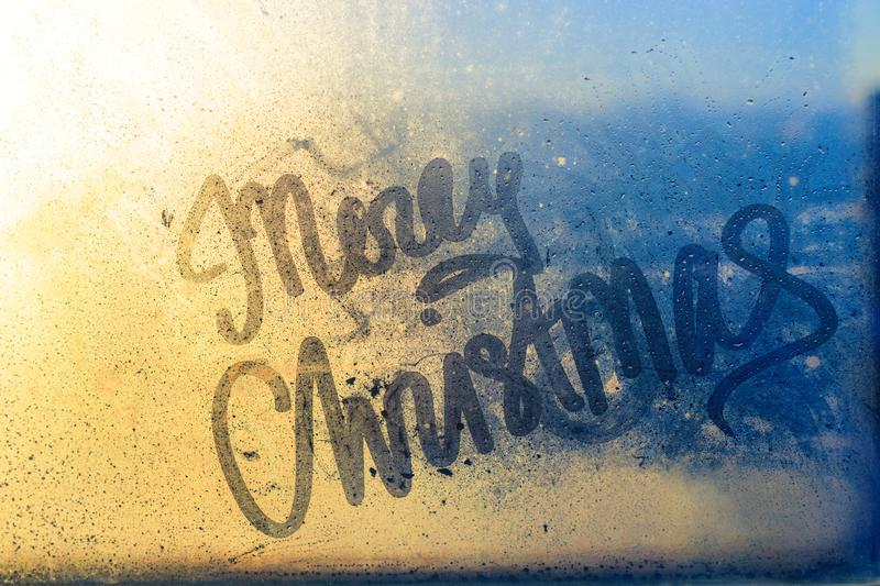 Merry Christmas written on wet window glass. At sunset light. Beautiful blue and yellow background of drops and splashes, concept for New Year and Christmas royalty free stock photography