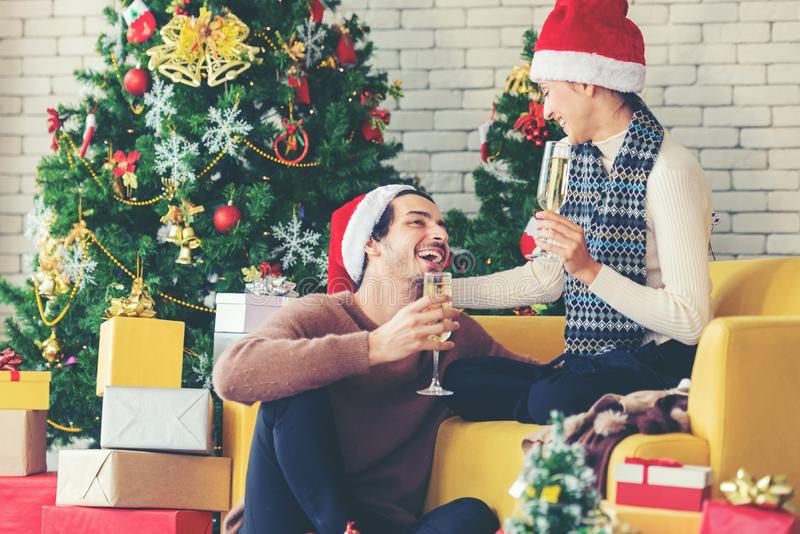 Merry Christmas. Young couple celebrating and party and drinking champagne new year and Christmas. With gift and Christmas tree at home stock photography