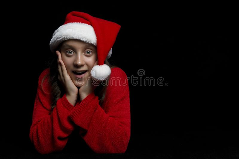 Merry Christmas. The young girl in a red sweater and Santa`s hat royalty free stock photos