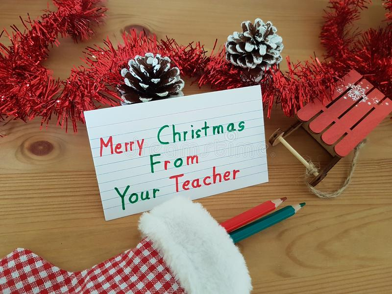 Merry Christmas From Your Teacher, Stocking With Colored Pencils, Pine Cone And Sled royalty free stock images