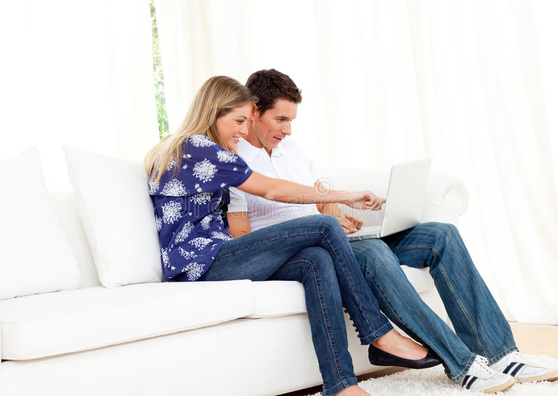 Download Merry Couple Using A Laptop Sitting On Sofa Stock Image - Image of happiness, computer: 13258931