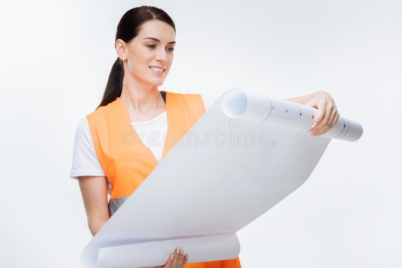 Merry female engineer stretching blueprint. Perfect project. Glad pensive female engineer examining blueprint and looking down while standing on the isolated royalty free stock photo
