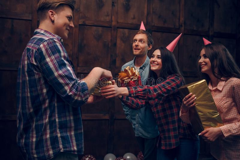 Amazing friends celebrate birthday and give presents to their friend. royalty free stock images