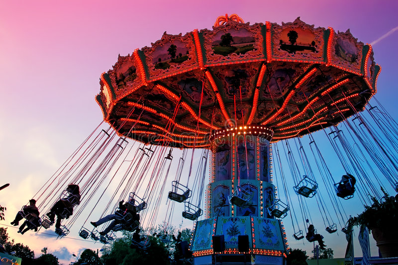 Merry-go-round. Spinning with people against the sunset sky stock photography
