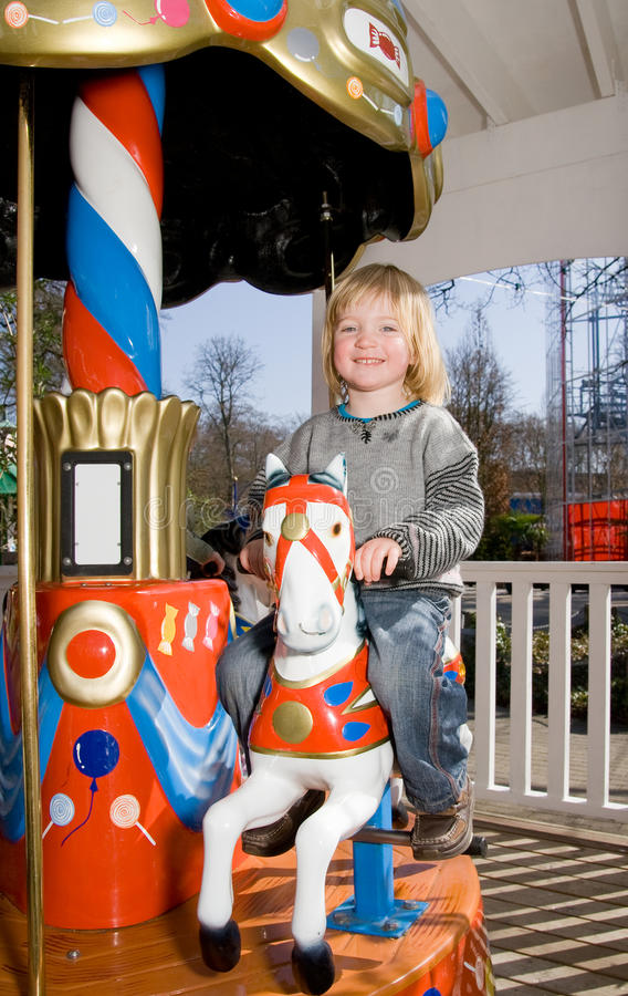 Merry-go-round horse carousel. Child on merry-go-round horse carousel. happy child on ride in fairground park stock images