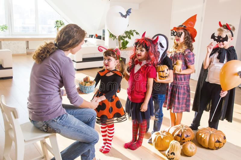 Family in Halloween party. Merry kids ask for a treat for a Halloween party stock photos