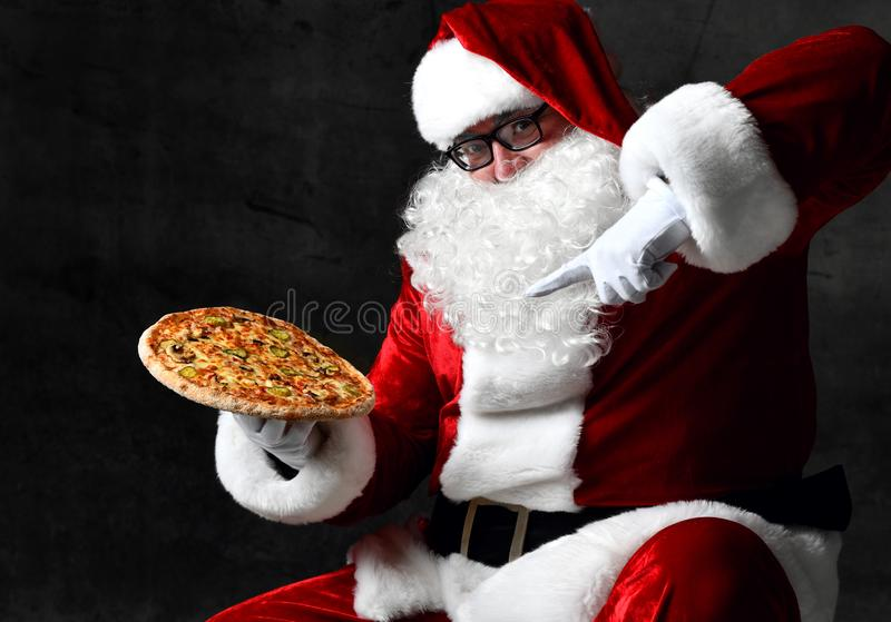 Merry laughing Santa Claus is pointing at big tasty pizza he is holding on his open palm. New year and Merry Christmas. Merry laughing Santa Claus is pointing at royalty free stock photography