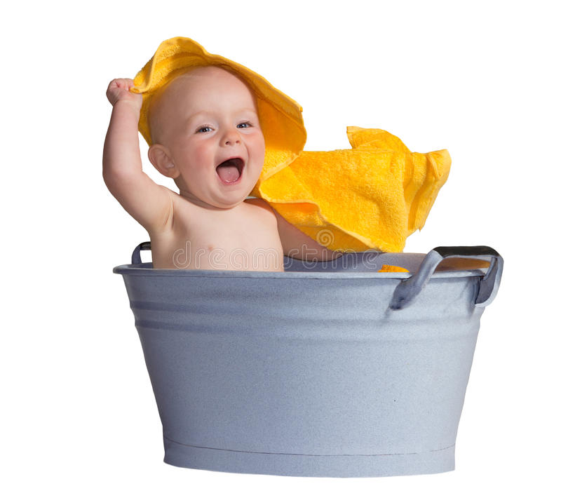 Merry little baby in a bath. Merry little baby laughing in excitement as it plays with a bright yellow towel while sitting in a zinc bath tub royalty free stock images