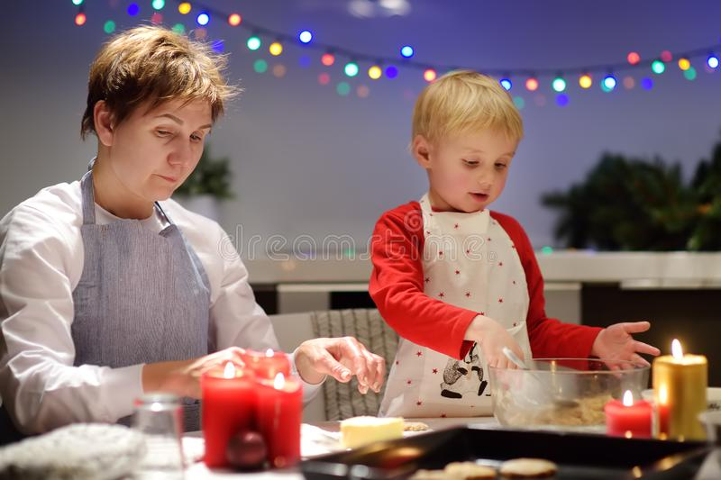 Merry little boy and his young grandmother bake cookies together during the holidays season. Christmas and New Year with kids stock images