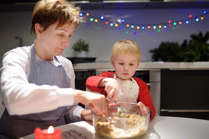 Merry little boy and his young grandmother bake cookies together during the holidays season. Christmas and New Year with kids royalty free stock photo