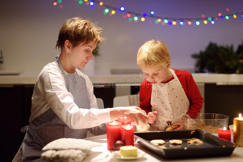 Merry little boy and his young grandmother bake cookies together during the holidays season. Christmas and New Year with kids royalty free stock photography